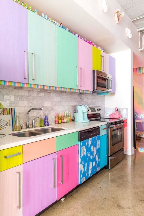 a colorful kitchen with all mismatching neon and pastel cabinets and a grey marble tile backsplash that calms the space down