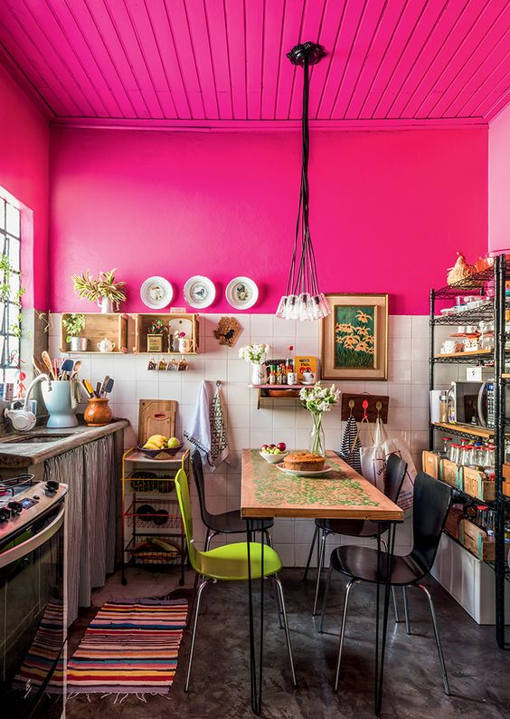 a colorful kitchen with hot pink walls and a ceiling, white square tiles and vintage cabinets and modern chairs is very bold