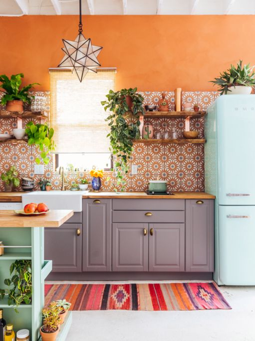 a colorful kitchen with orange walls, grey cabinetry, a mint blue fridge, a matching kitchen island and a bold orange printed tile backsplash
