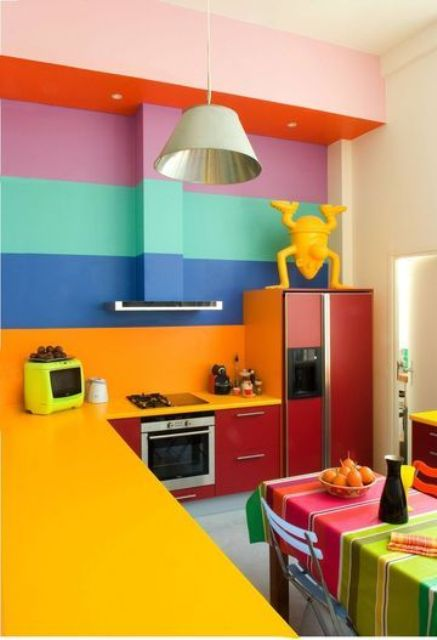 a colorful kitchen with red cabinets, sunny yellow countertops, a bold rainbow striped wall and bright striped textiles
