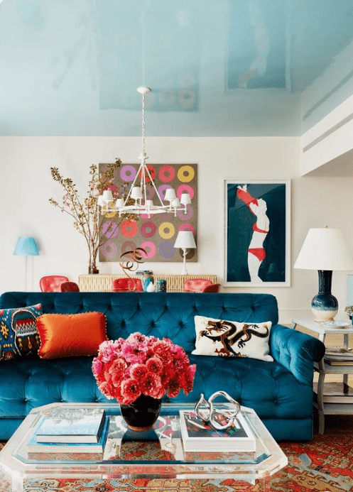 a colorful living room with a navy sofa, orange and red touches, bright artworks and a bold printed rug