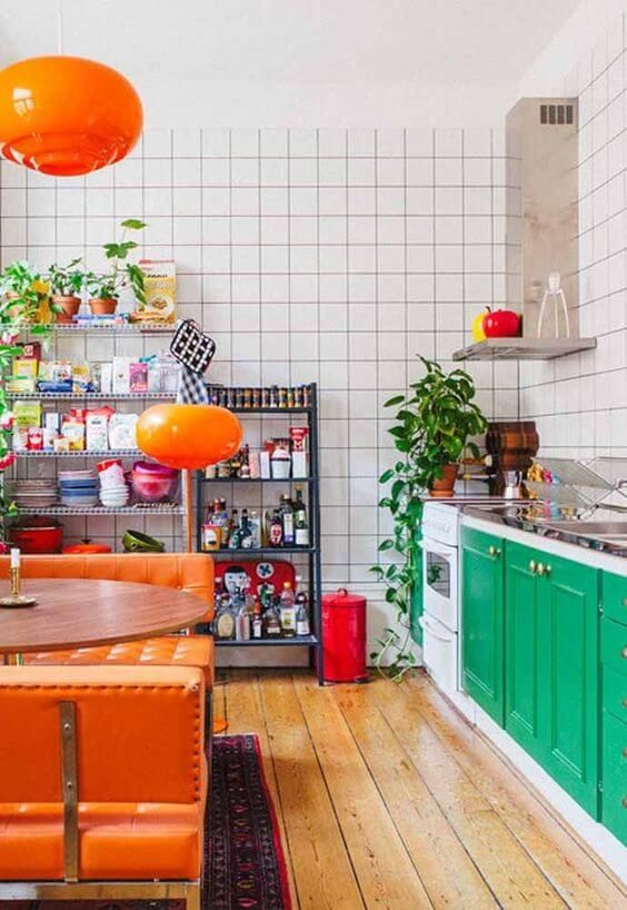a colorful retro kitchen with emerald cabinetry, orange leather benches and a round table, bright pendant lamps and potted plants