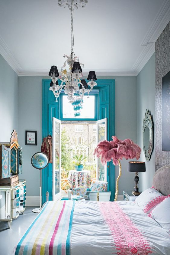 a colorful whimsical bedroom with blue shutters, bright bedding, a feather tree and a mirror dresser with wallpaper inside