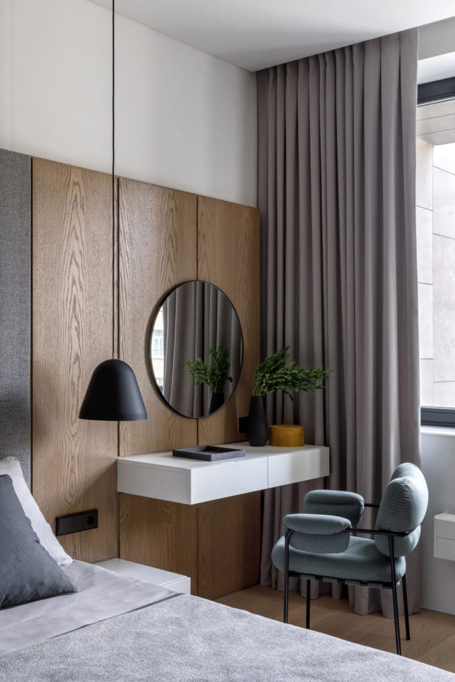 a contemporary beauty nook with a floating vanity, a round mirror, a comfy upholstered chair and light from the window