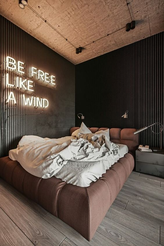 a contemporary bedroom with black slab walls, an upholstered bed, a neon sign as the main light source in the room