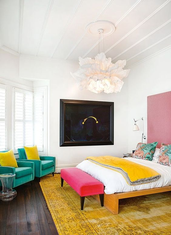 a contemporary colorful bedroom with green chairs, a pink bench, a yellow rug and blanket plus a pink wallpaper accent wall