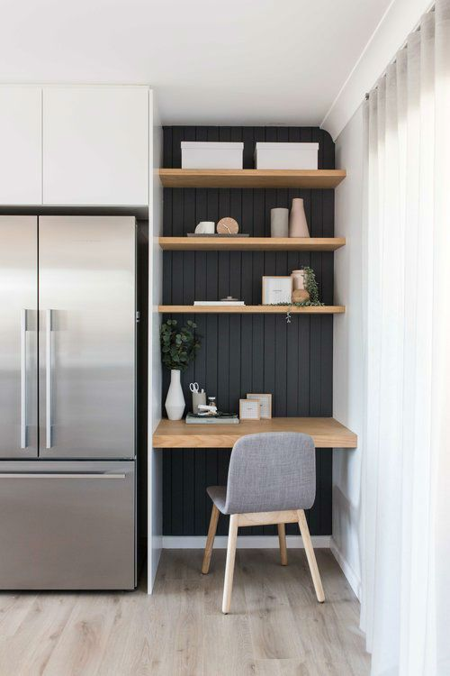 a contemporary farmhouse kitchen with white cabinetry and a working space with a black wall and built in shelves and a desk plus a grey chair