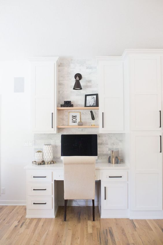 a cool white kitchen with a matching built-in desk and cabinets, marble tiles on the wall and built-in shelves plus a comfy chair