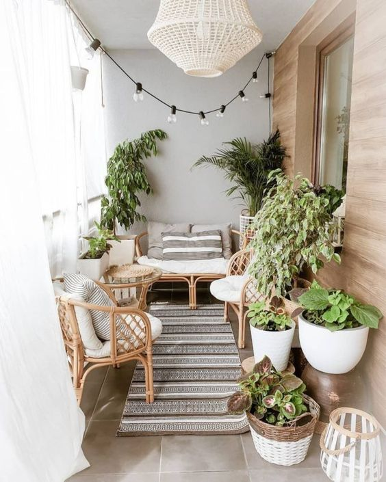 a cozy modern balcony with cool rattan furniture, printed textiles and potted plants plus lights over the space