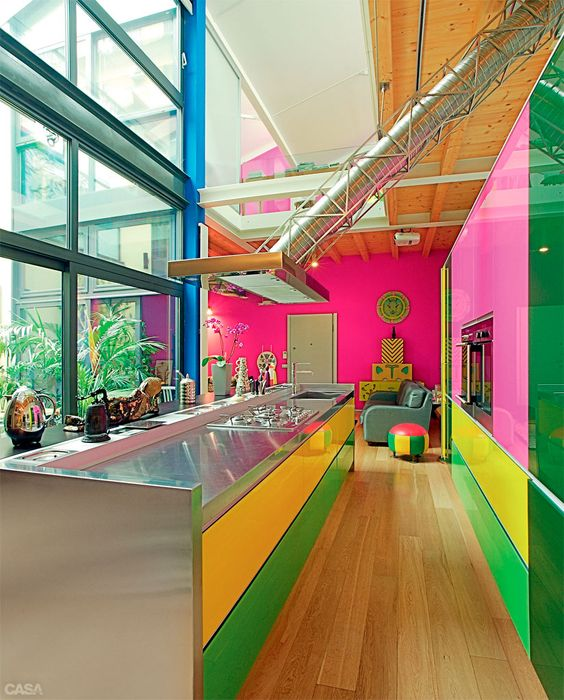 a crazily colorful kitchen in hot pink, bold yellow and green and metal surfaces looks ultra-modern, super bold and super catchy