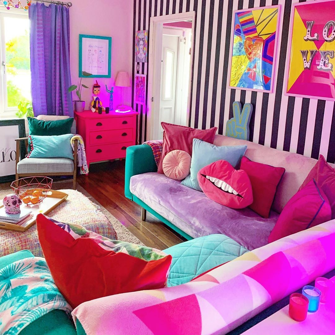 a crazily colorful living room with a striped accent wall and other walls done in pink, a lilac and green sofa, colorful pillows and bold artworks and a hot pink dresser