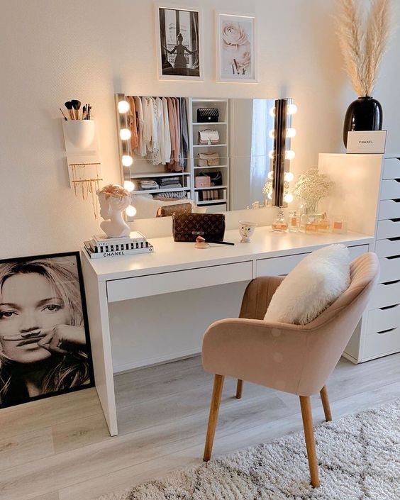 a cute glam makeup space with a white vanity, a storgae unit next to it, a lit up mirror, a pink chair and artworks