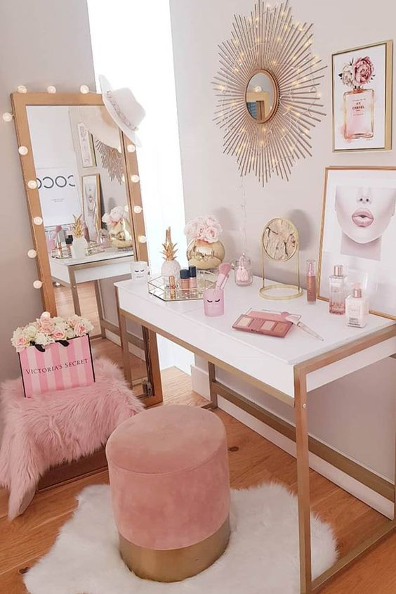 a cute glam nook with a vanity, severla mirrors, lights, a pink pouf and an additional faux fur one