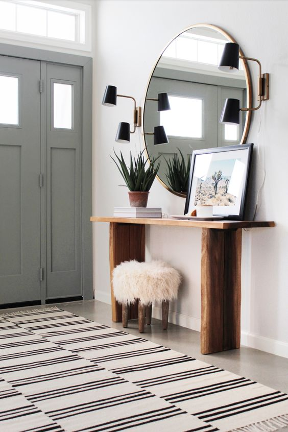 a cute modern entryway with a round mirror, a wooden console, a faux fur stool, wall sconces and a potted plant