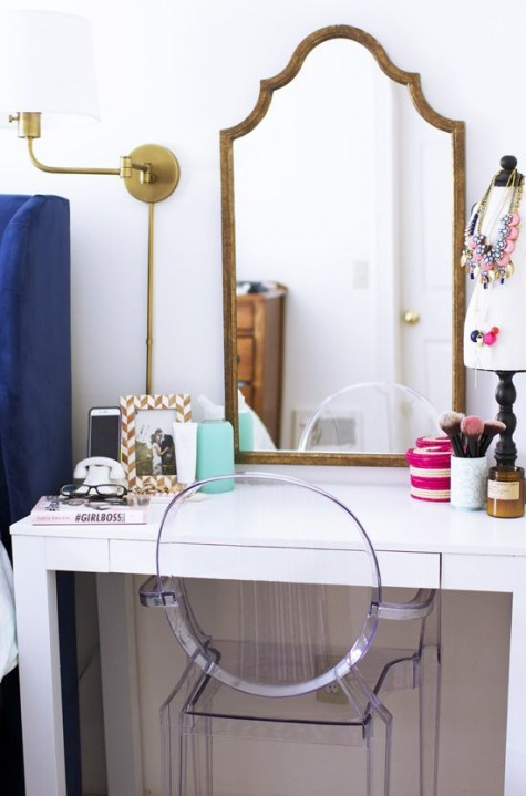 a cute modern makeup nook with a white vanity, a refined vintage mirror and a sconce is comfy and cool