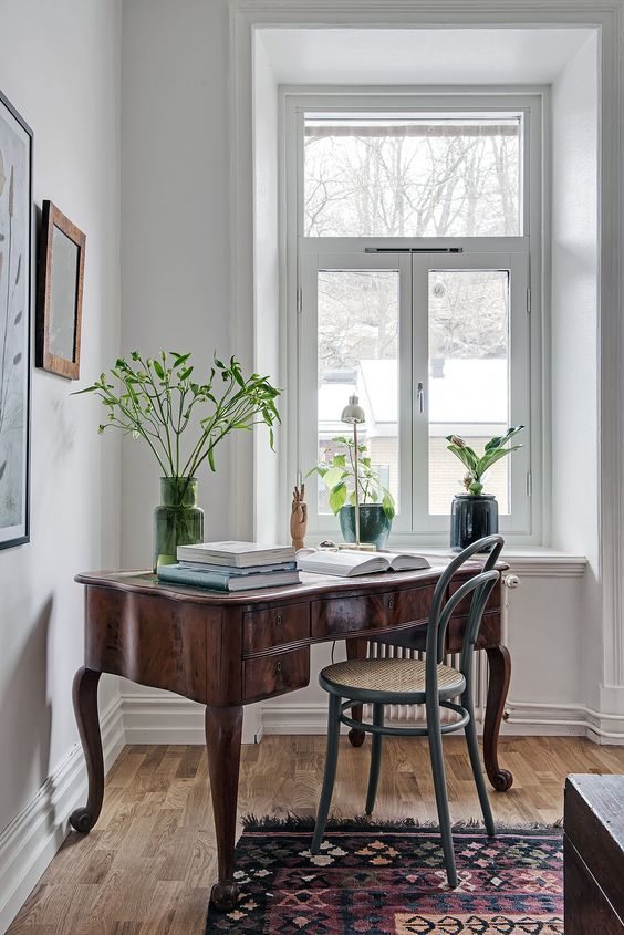 a dark stained vintage wooden desk, a blue rattan chair, potted plants and a small gallery wall create a chic nook for working