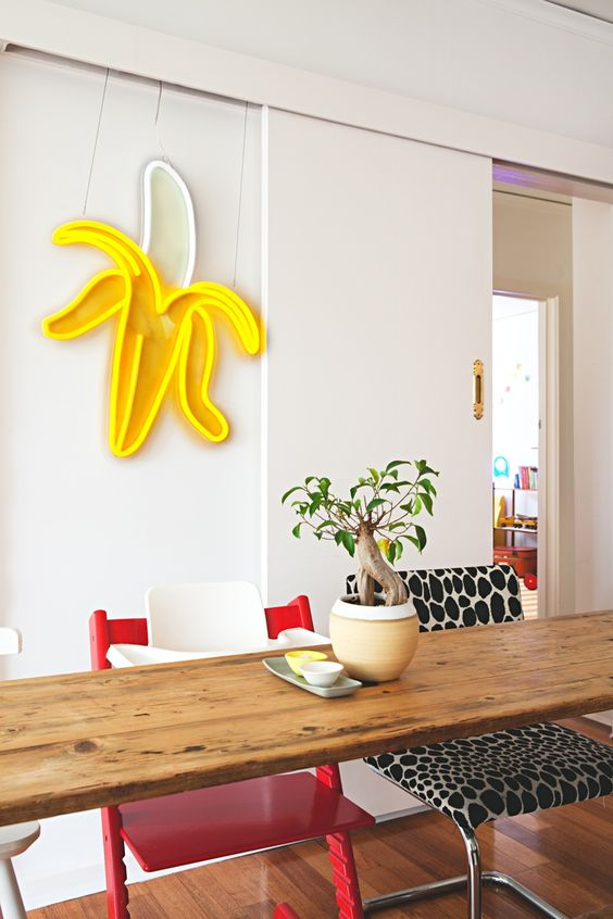 a funky dining zone with mismatching chairs and a cool banana neon light on the wall for a bit of fun