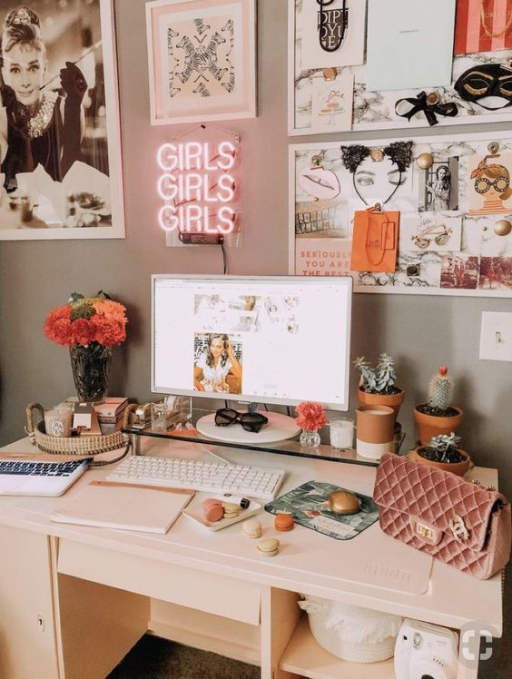 a girlish work and study space with a fun memo board over the desk, pink touches and a small pink neon sign