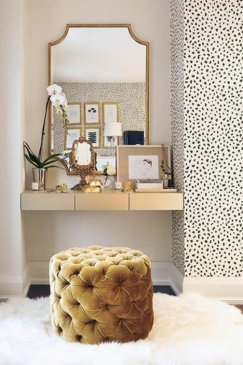 a glam beauty nook with a built in vanity with storage drawers, a large mirror and a tufted ottoman as a seat