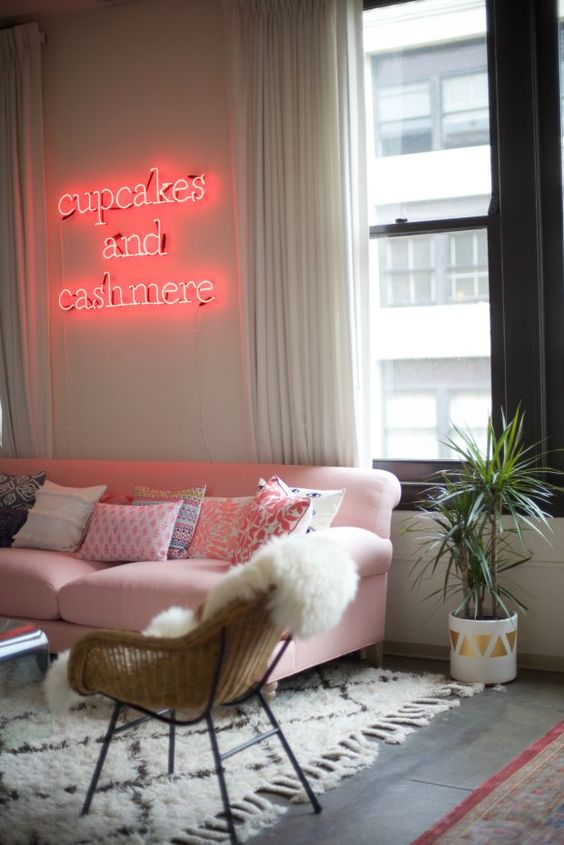 a glam living room with a pink sofa and a pink neon light over it is very welcoming and very cool
