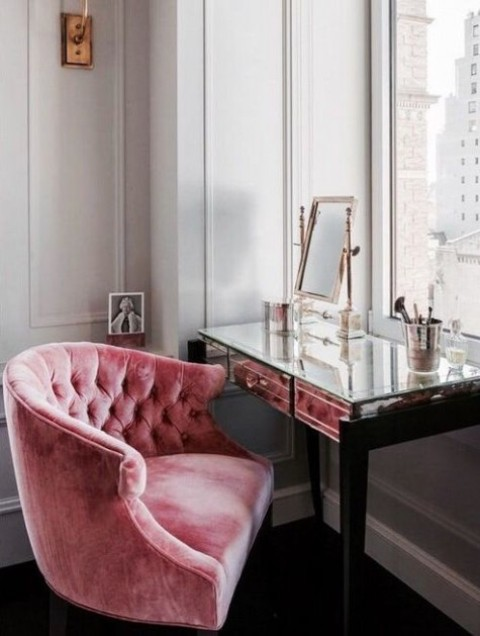 a glam makeup nook with a chic mirrored vanity by the window, a mirror and a pink velvet chair for a glam person