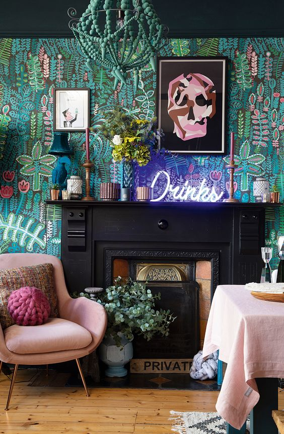 a gorgeous maximalist living room with botanical wallpaper, a non-working fireplace, pink furniture and a cool sign showing the bar is near