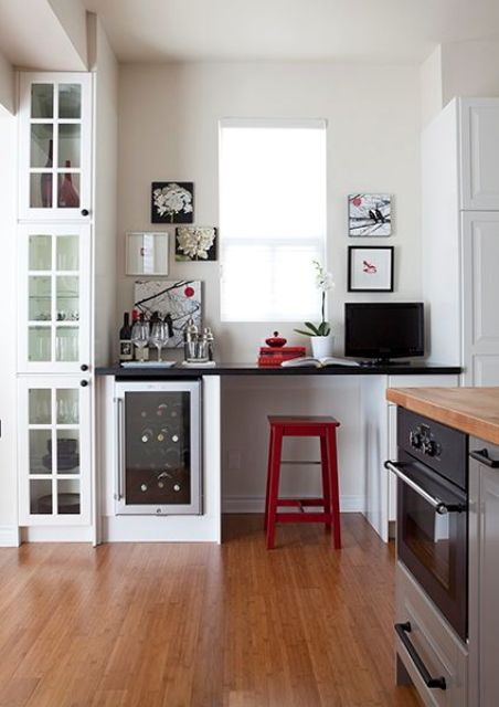 a grey farmhouse kitchen with a working space, a white desk with a black countertop, a cooler and a fridge by its side