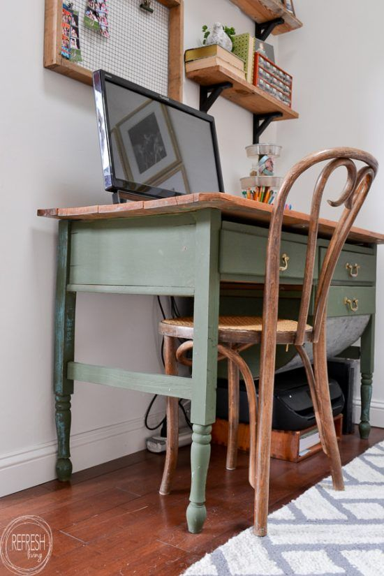 a home office with a green desk with a stained desktop, a vintage wooden chair and rustic shelves attached to the wall
