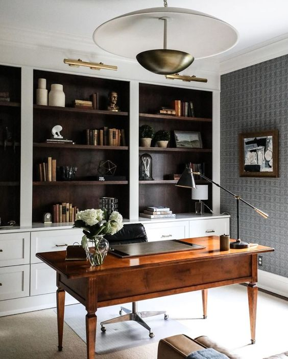 a home office with built-in shelves, a stained desk, a pendant lamp and a black and white artwork plus brass touches