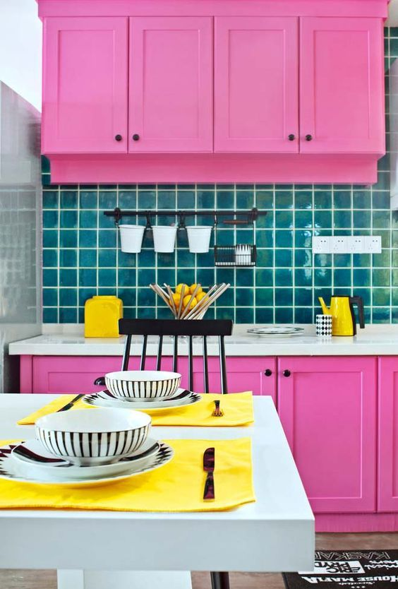 a hot pink kitchen with a blue tile backsplash and yellow touches and linens is a fun and bold space