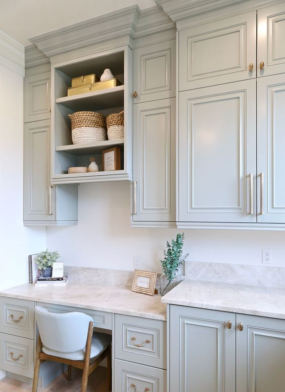 a light blue kitchen with stone countertops and a built-in matching desk plus some cabinets over it for working