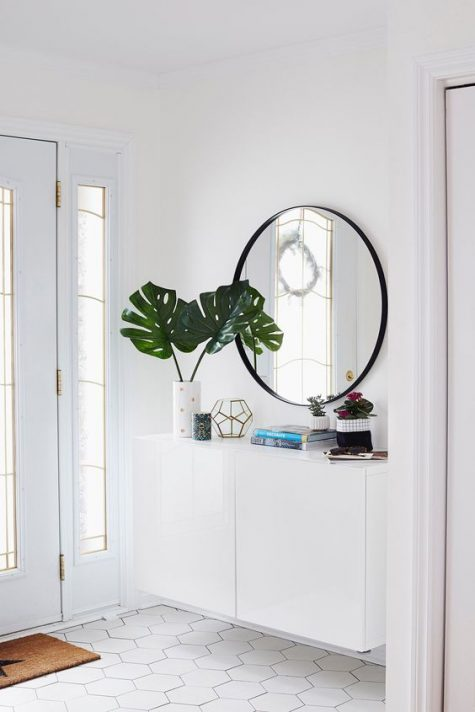 a light-filled entryway with a floating console, a round mirror, vases and a candle lantern