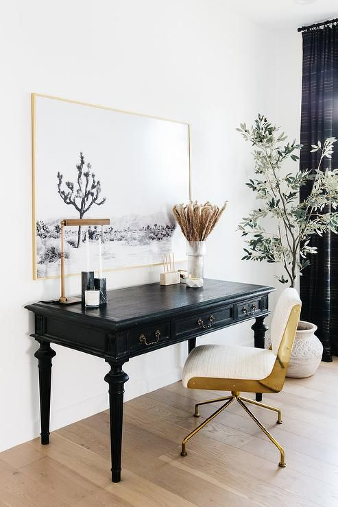 a lovely home office space with a black vintage desk, a white and gold chair, a statement artwork in a gold frame and black curtains