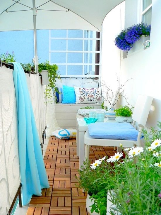 a lovely summer balcony with neutral furniture, blue and printed textiles, an umbrella and some potted greenery and blooms