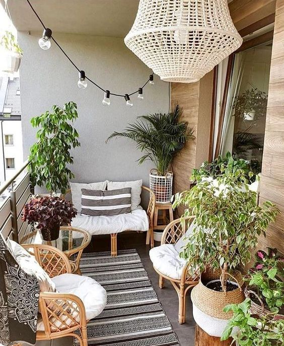 a lovely summer balcony with rattan furniture, potted plants, a woven chandelier and a string of lights is amazing