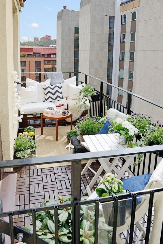a lovely summer balcony with wooden furniture, potted plants and blooms and printed textiles is a cool space to be
