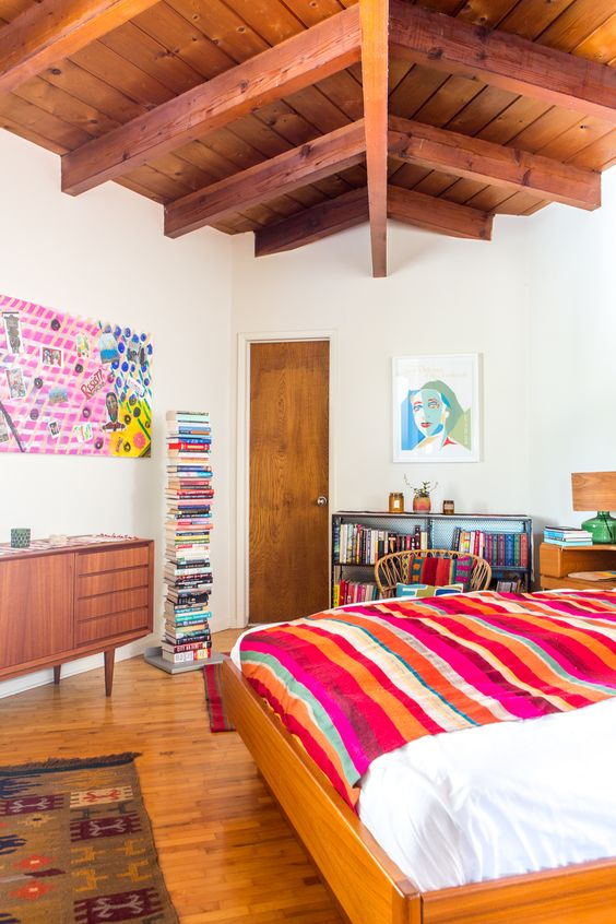a mid-century modern bedroom with bright bedding, artworks and even books that bring color to this room
