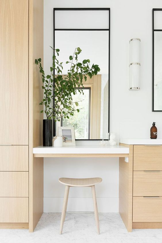 a minimalist beauty nook with a built in vanity, a small stool and a large mirror plus a sconce on the wall for more light here