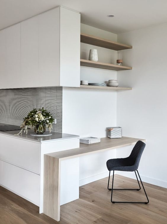 a minimalist white kitchen with a grey countertop and a matching backsplash, a small countertop desk and built in shelves that form a workspace