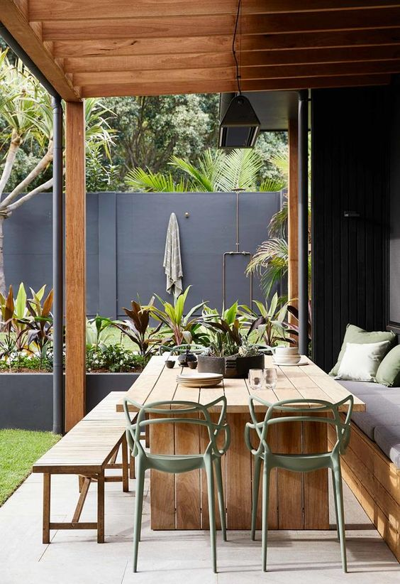 a modedrn semi-outdoor dining space with a wooden table and benches, modern green chairs and a pendant lamp over the space