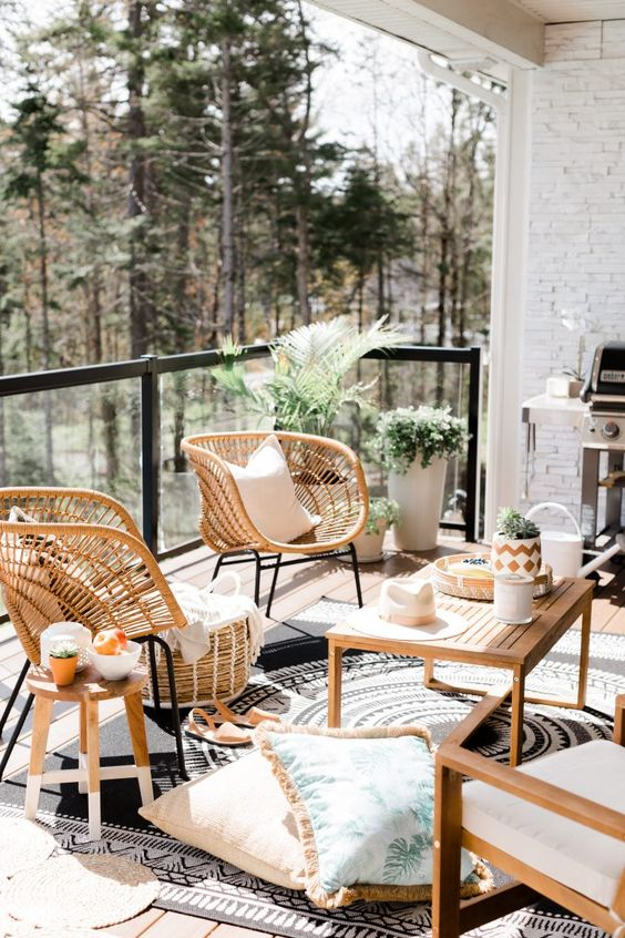 a modern boho balcony with simple wooden and cool rattan chairs, printed rugs and pillows and potted plants
