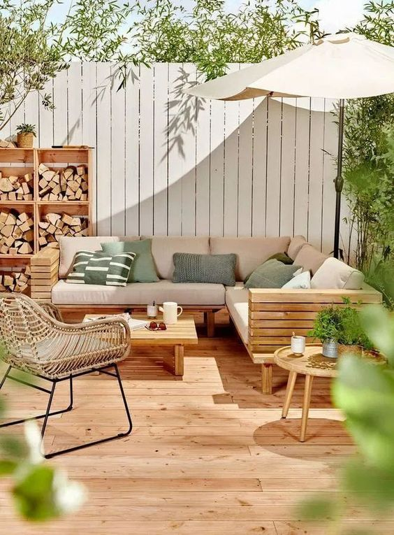 a modern deck with a wooden sectional sofa, a rattan chair and a low coffee table, green printed pillows and a firewood storage unit