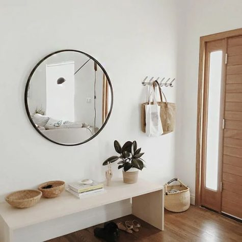 a modern entry with a sleek bench, a round mirror, some baskets and a clothes rack is welcoming and airy