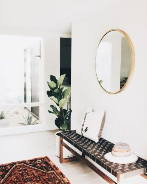 a modern entryway with a leather woven bench, a boho rug and a round mirror plus a statement plant