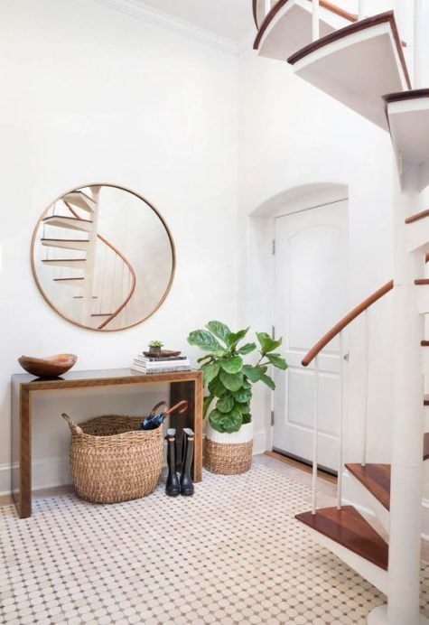 a modern entryway with a wooden sleek console, a round mirror, some baskets and a statement plant is very cozy