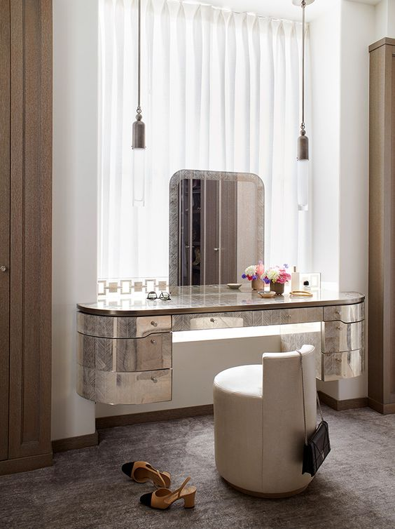 a modern glam beauty nook with a mirror wall mounted vanity, pendant lamps, a round chair and much light form the window