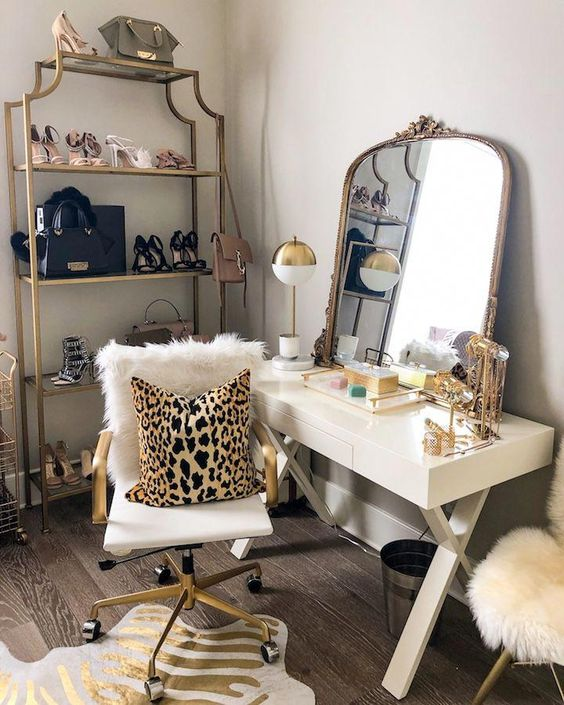a modern glam makeup nook with a white trestle vanity, a white and gold chair, a mirror in a refined frame and a lamp