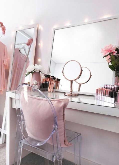 a modern glam makeup space with a narrow console with a glass top, a couple of mirrors and a ghost chair plus blooms