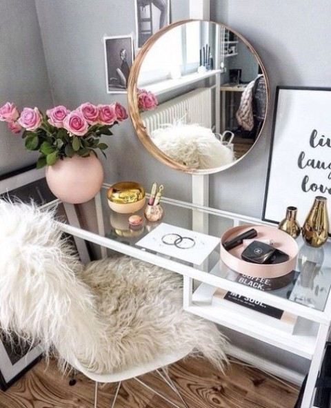 a modern glam makeup space with an IKEA Vittsjo desk as a vanity, a round mirror and a faux fur chair