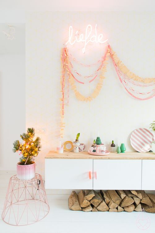 a modern glam space in white and with pink items and details, with a pink neon sign that adds more fun to the room